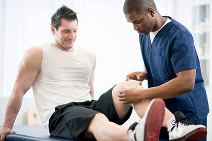 Sports physical therapy resident wrapping a patient's knee